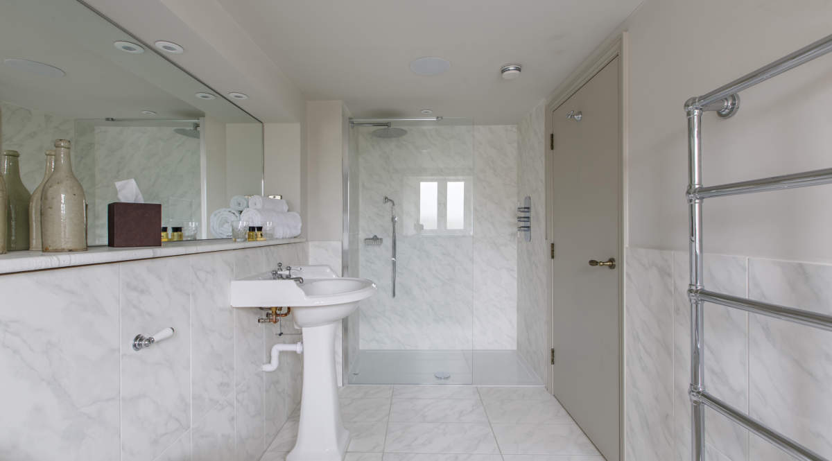 Large en-suite featuring large walk-in shower and dual bathing bath